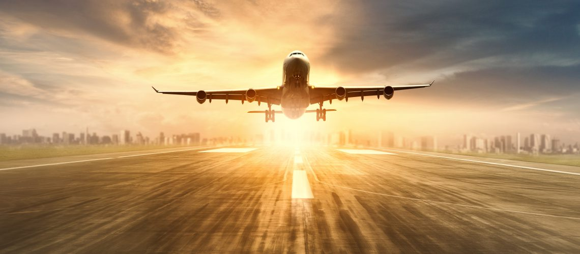 air plane flying over airport runway with city scape and sunset sky background